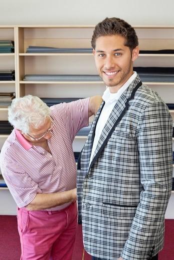 Palm Desert, California, USA. Senior tailor measuring young customer for making suit : Stock Photo