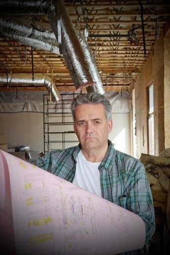 Stock Photo: 1654-50587 Palm Desert, California, USA. Portrait of mature architect with blueprint at construction site