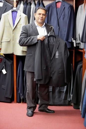 Stock Photo: 1654-50752 London, UK. Full length portrait of man shopping for formal coat in menswear store