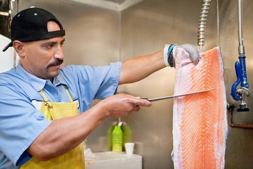 Los Angeles, California, USA. Mature fishmonger slicing salmon fish : Stock Photo