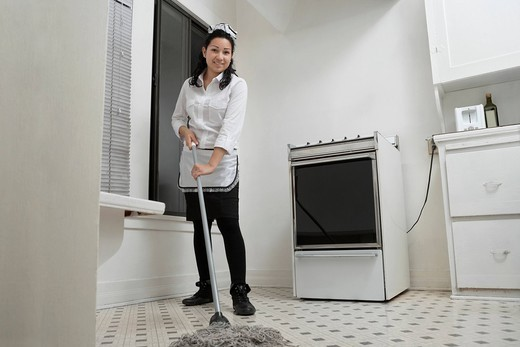 Los Angeles, California, USA. Full length portrait of young housemaid cleaning floor with mop : Stock Photo