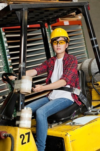 Los Angeles, California, USA. Asian female industrial worker driving forklift truck : Stock Photo