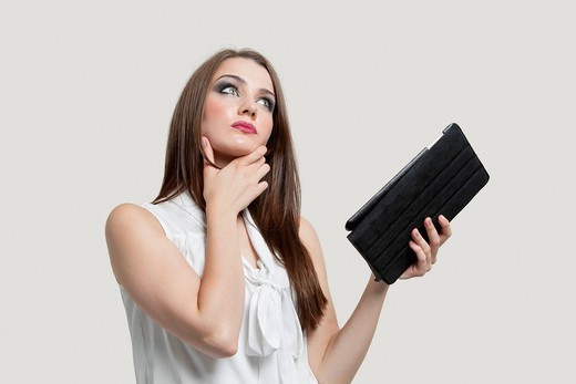 London, UK. Pensive young woman holding tablet PC over gray background : Stock Photo