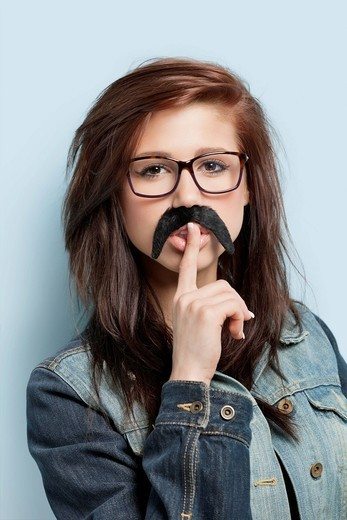 London, UK. Portrait of young woman with fake mustache and finger on her lips against light blue background : Stock Photo