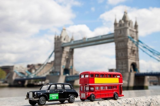 London, UK. Public transport figurines with London Bridge in the background : Stock Photo