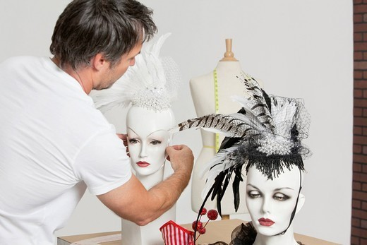 Palm Springs, California, USA. Back view of male fashion designer adjusting feather fascinator on mannequin : Stock Photo