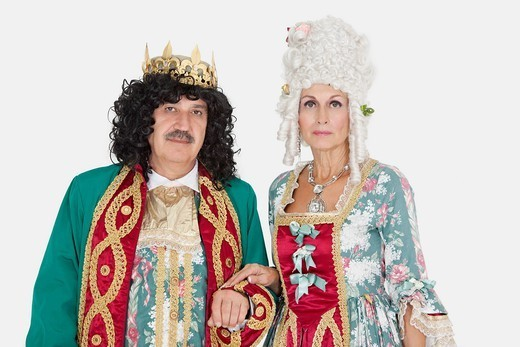 Palm Springs, California, USA. Portrait of senior king and queen standing over gray background : Stock Photo