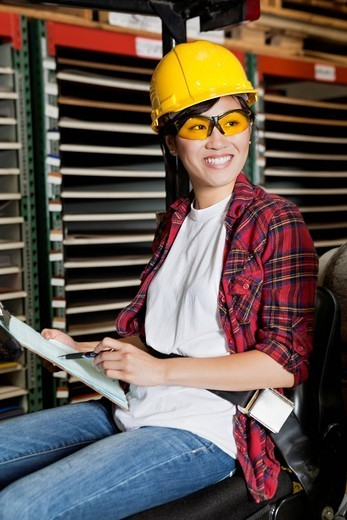 Los Angeles, California, USA. Asian female industrial worker looking away while holding clipboard : Stock Photo