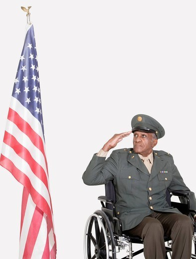 Palm Springs, California, USA. Senior male US military officer in wheelchair saluting American flag over gray background : Stock Photo