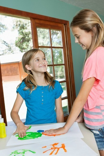 Palm Springs, California, USA. Happy young sisters making hand prints on paper : Stock Photo