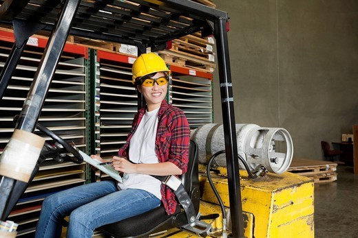 Los Angeles, California, USA. Asian female industrial worker with clipboard looking away while sitting in forklift truck : Stock Photo