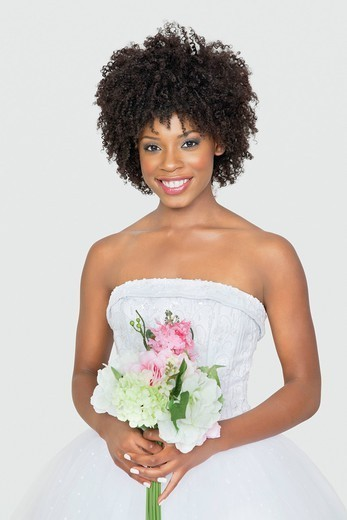 Palm Springs, California, USA. Portrait of an attractive African American bride holding bouquet over gray background : Stock Photo