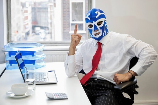 London, UK. Portrait of businessman in wrestling mask points up at office desk : Stock Photo