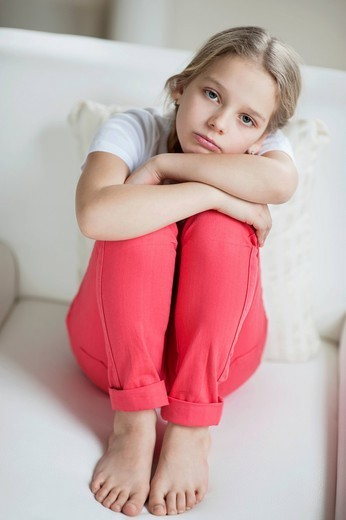 Prague, Czech Republic. Portrait of sad girl sitting on sofa : Stock Photo