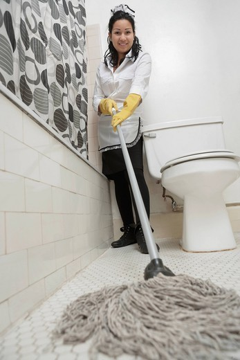 Stock Photo: 1654-54251 Los Angeles, California, USA. Full length portrait of maidservant cleaning bathroom floor