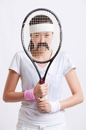 Studio. Portrait of young woman with a fake mustache holding tennis racket in front of her face against white background : Stock Photo