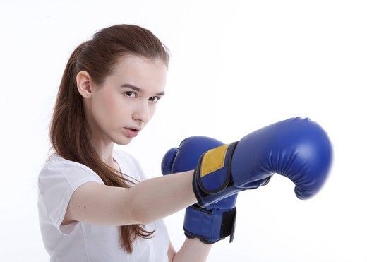 Studio. Portrait of young Caucasian woman with boxing gloves against white background : Stock Photo