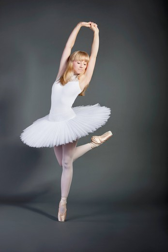 Studio. Young woman in white tutu performing ballet over grey background : Stock Photo