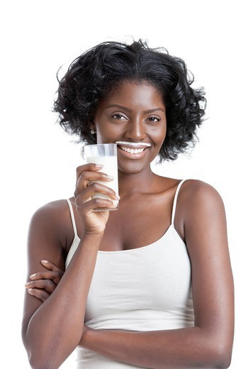 Studio. Portrait of happy young woman with milk moustache holding glass of milk : Stock Photo