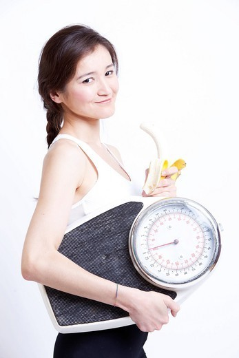 Studio. Side view of young Asian woman holding banana and weight scale against white background : Stock Photo