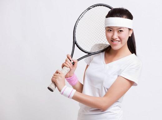Studio. Portrait of happy female tennis player holding racket against white background : Stock Photo