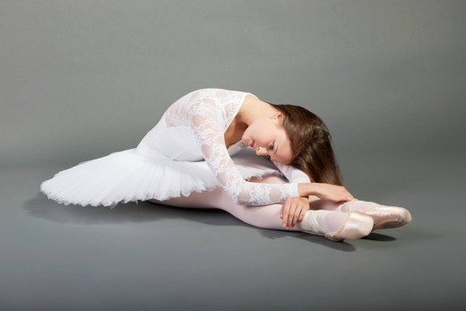 Studio. Young ballet dancer wearing white tutu sitting over grey background : Stock Photo