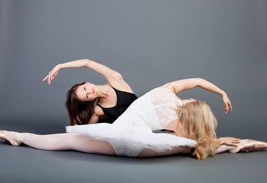 Studio. Two young female ballet dancers doing the splits over grey background : Stock Photo