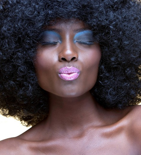 Studio. Close_up view of beautiful woman with afro blowing a kiss : Stock Photo