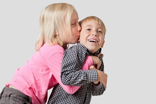 Studio. Young girl kissing and embracing brother over white background : Stock Photo