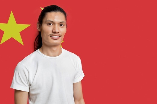 London, UK. Portrait of young mixed race man standing against Chinese flag : Stock Photo