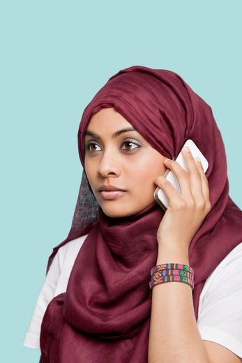 London, UK. Young Muslim woman in maroon headcloth using cell phone against blue background : Stock Photo