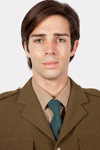 London, UK. Portrait of young man in military uniform against gray background : Stock Photo