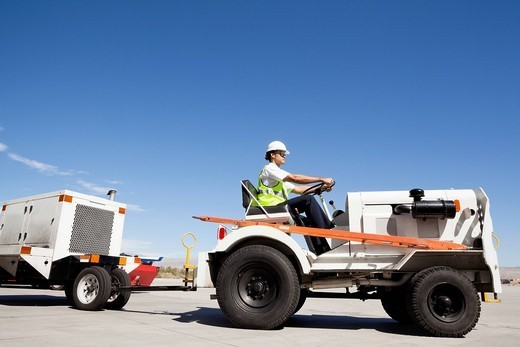 Palm Springs, California, USA. Young male ground crew driving truck at airport runway : Stock Photo
