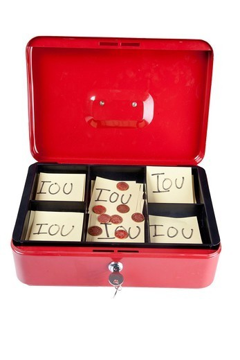 London, UK. Open box with IOU notes and coins over white background : Stock Photo