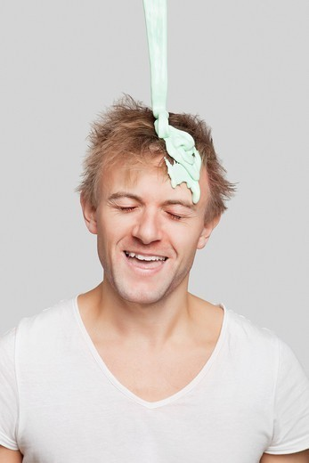 Stock Photo: 1654-56721 London, UK. Paint falling on young Caucasian man's head against gray background
