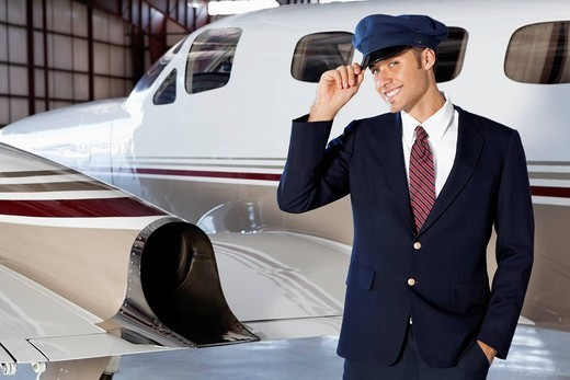 Palm Springs, California, USA. Portrait of handsome young pilot standing in front of private airplane : Stock Photo
