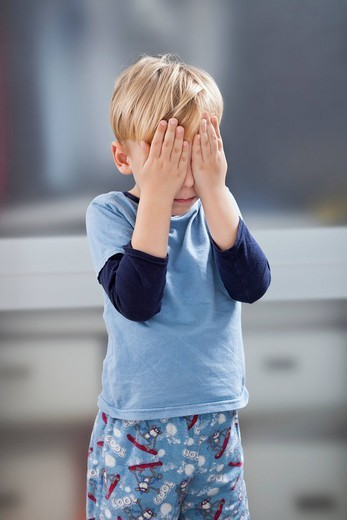London, UK. Scared little boy in casuals with hands over his eyes : Stock Photo