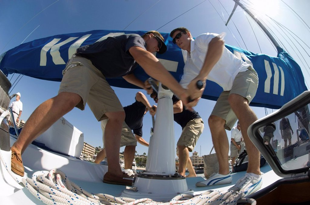 Sailors operating windlass on yacht low angle view : Stock Photo