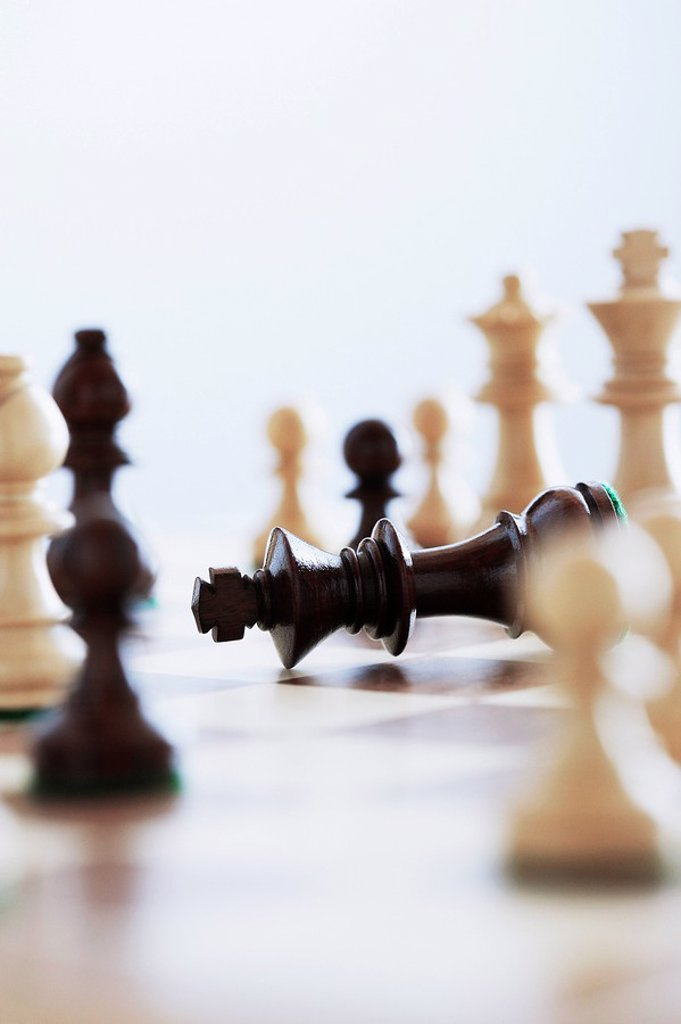 Chess game king lying on board surrounded by pieces : Stock Photo