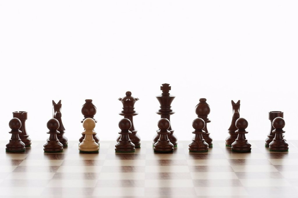 Single white pawn in initial line up of black chess pieces : Stock Photo