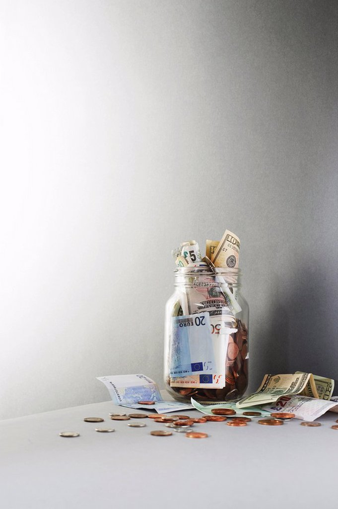 Notes and coins overflowing from jar : Stock Photo
