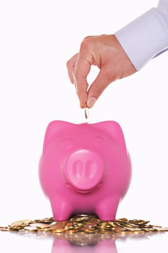Stock Photo: 1654R-10220 Man putting money in overflowing piggy bank close up of hand