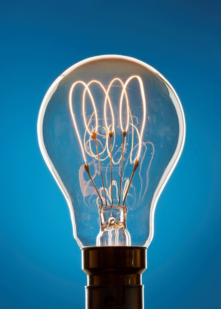 Transparent light bulb against blue background in studio : Stock Photo