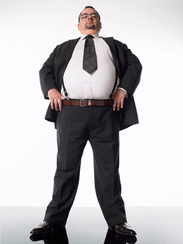 Overweight businessman standing with thumbs in belt : Stock Photo