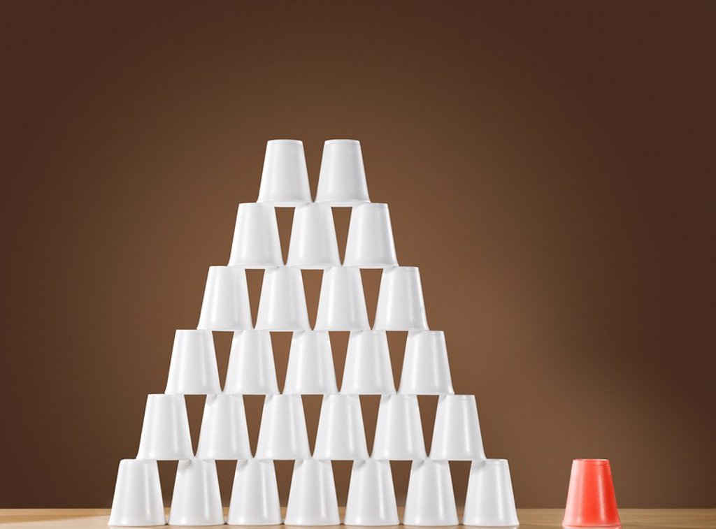 Pyramid of white plastic cups on table next to single red cup : Stock Photo