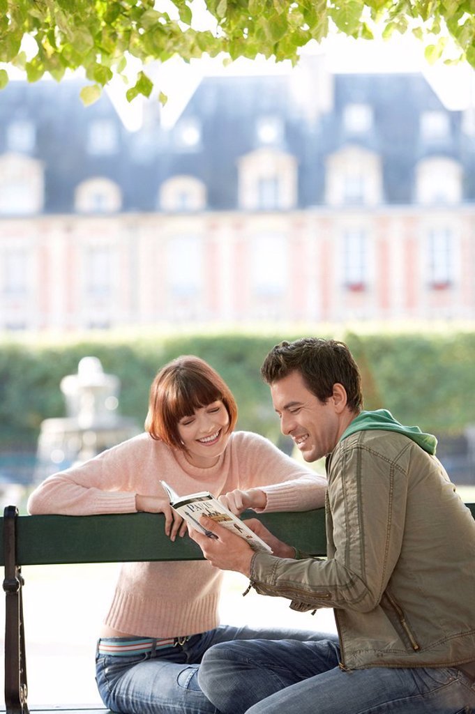 Stock Photo: 1654R-10624 Young couple reading guide book sitting on bench in park