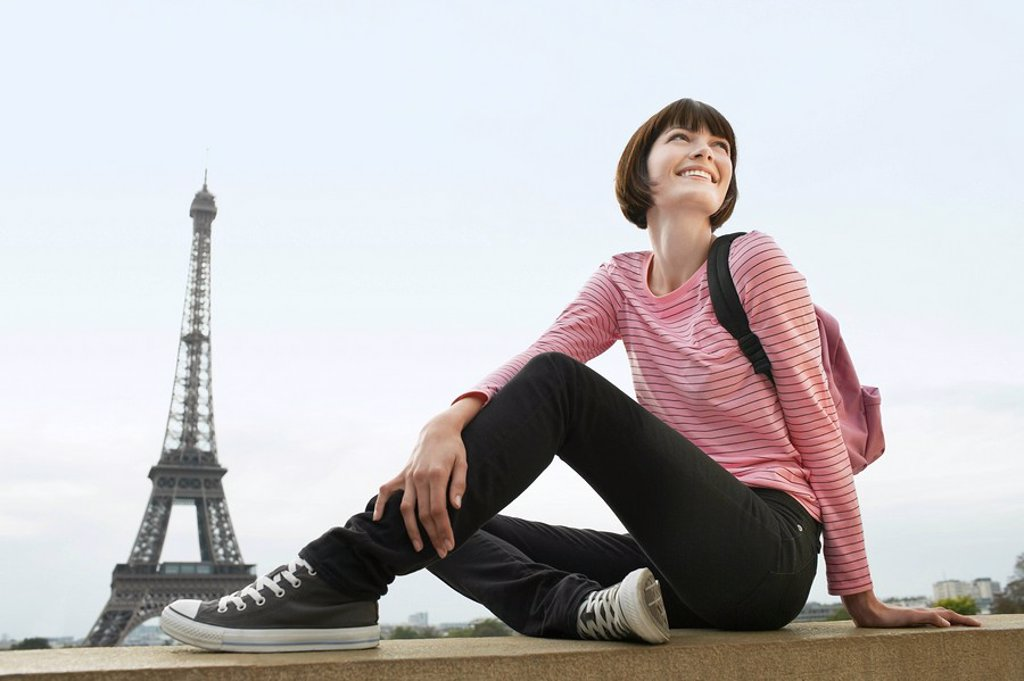 Stock Photo: 1654R-10627 France Paris Young woman sitting on balcony in front of Eiffel Tower