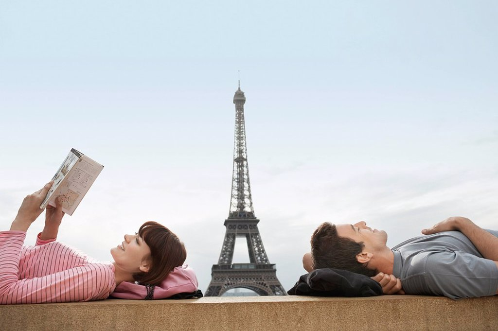 Couple lying on ledge of the Trocadero with Eiffel Tower viewed in the background : Stock Photo