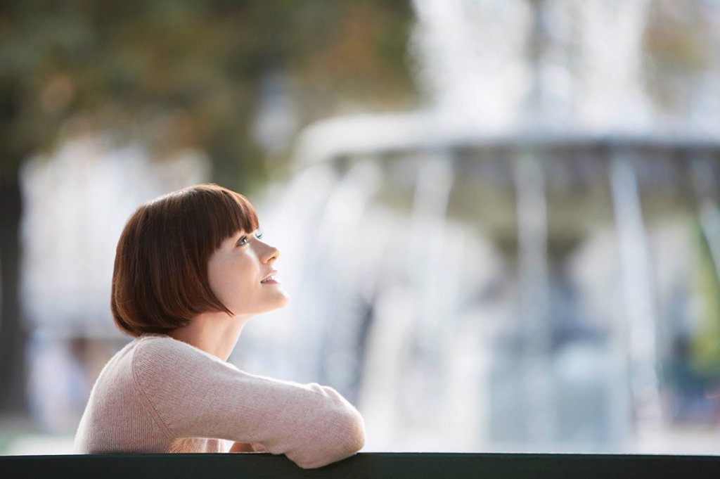 Young woman sitting on bench in front of fountain head and shoulders : Stock Photo