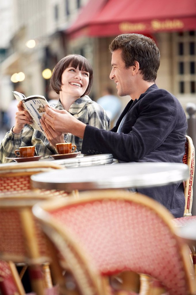 France Paris Couple reading guide book sitting outside cafe : Stock Photo